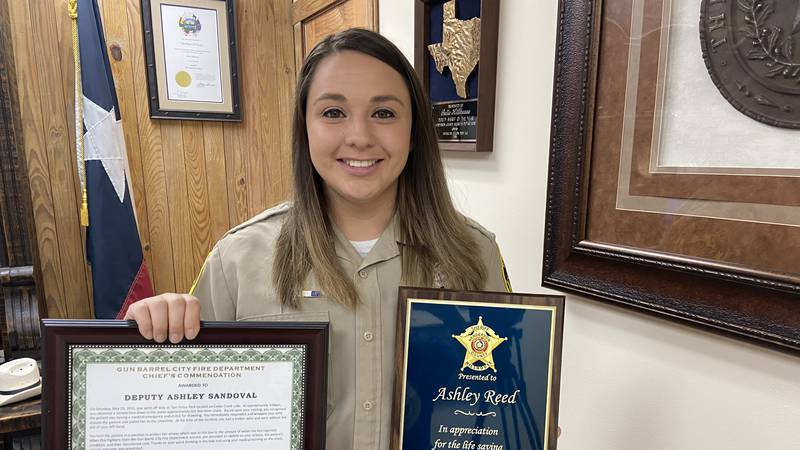 Henderson County Deputy Ashley Reed holding a certificate and plaque she was honored with for...