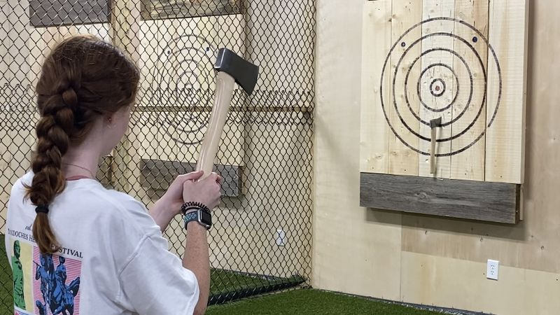 Visitor of Lumberjack Axe Throwing lines up a shot