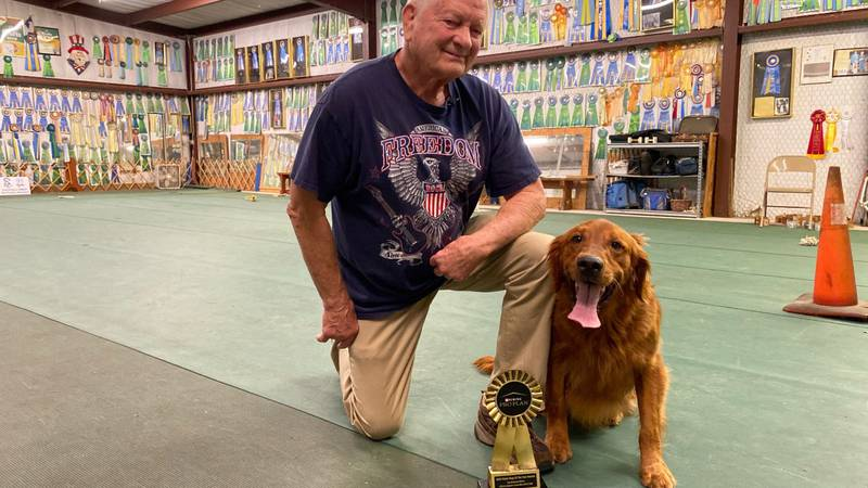 David Gannon and his six-year-old golden retriever, Trap, pose with their new trophy for...