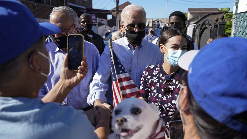 President Joe Biden talks with people as he tours a neighborhood impacted by flooding from the...