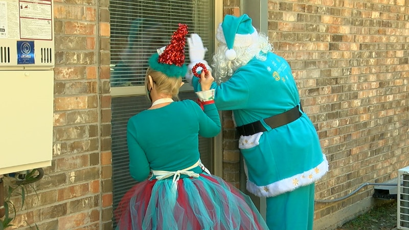 Chyrstal Hudson and Santa Clause knocking on a window at the Joseph House to bring joy to...