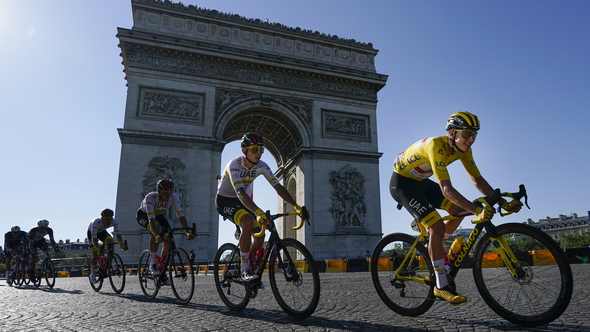 Slovenia's Tadej Pogacar, wearing the overall leader's yellow jersey, passes the Arc de...