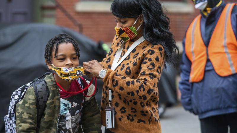 In this Monday, March 29, 2021, file photo, Jenea Edwards, of the North Side, helps her son...