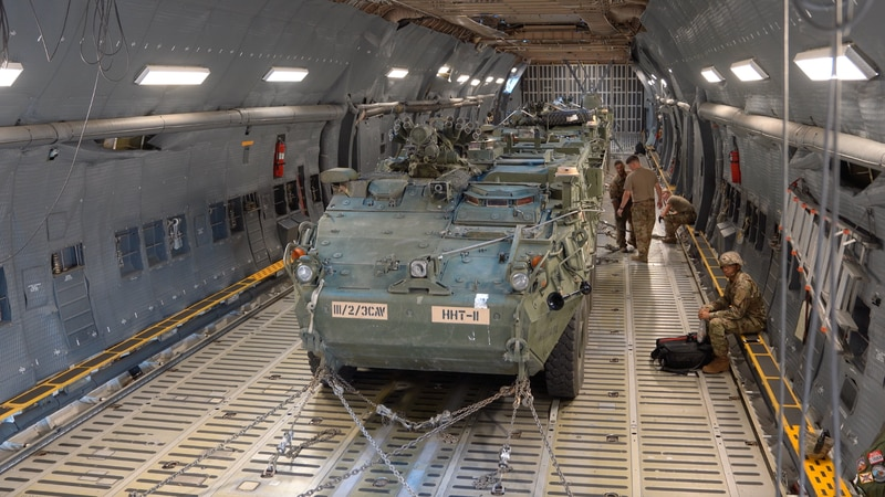 Soldiers with Fort Hood's 3d Cavalry Regiment load three eight-wheeled 18-ton Stryker vehicles...