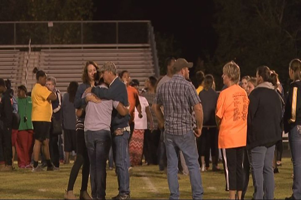 Alto football players and community members gather on the football field at a prayer rally in...