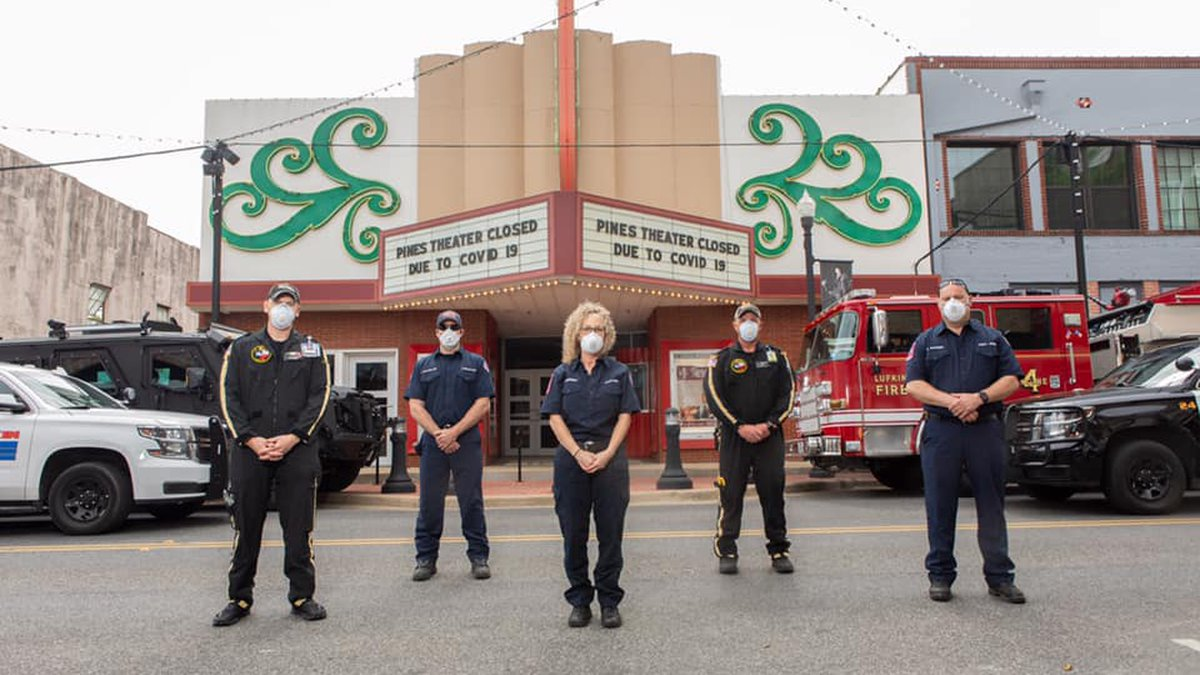 Lufkin first-responders standing in front of The Pines Theater in masks