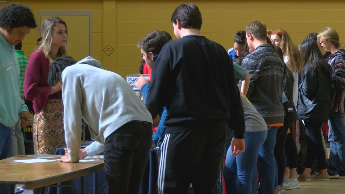 Students gather around a college recruitment table at NHS College Fair.
