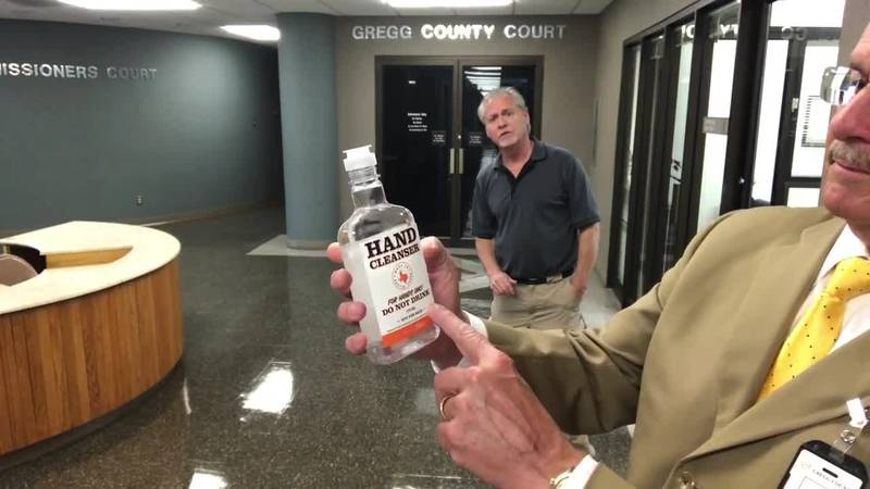 Gregg County Judge Bill Stoudt holds up a bottle of hand sanitizer donated to his office by...