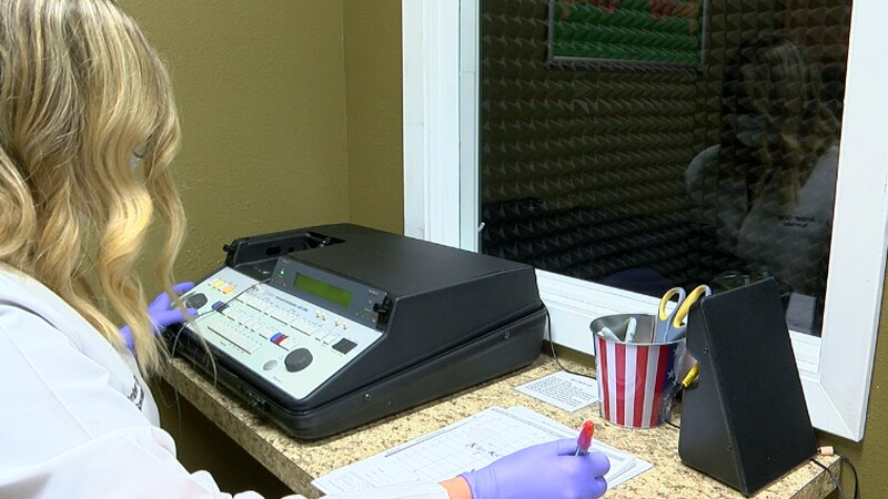Amber Gray, a Licensed Hearing Instrument Specialist, running a hearing test.