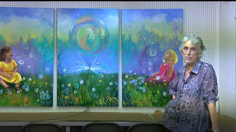 Lavon Hopkins, one of five Zavalla artists, stands in front of a three-panel mural they created...