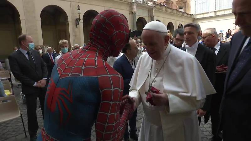 A man dressed as Spider-Man to cheer up sick kids gives Pope Francis a superhero mask.