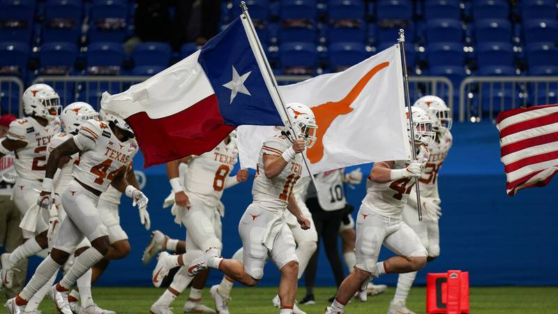 Texas players run onto the field for the Alamo Bowl NCAA college football game against...
