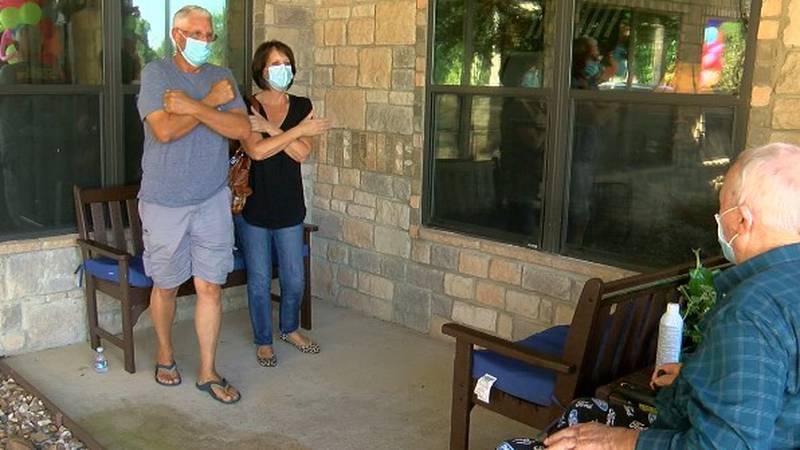 Teresa and David Cutright air-hug Teresa's father, Richard Daniel, at their visit.